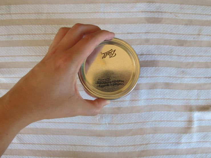Adding canning rings to jars, finger tight.