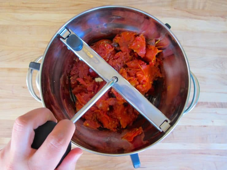 Running crushed, roasted tomatoes through a food mill.