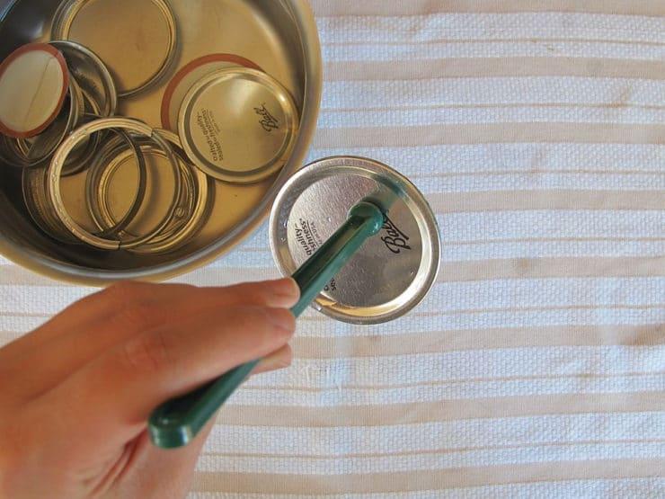 Using a lid lifter on sterilized jar lids.
