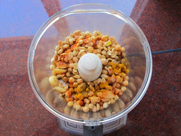 Chickpeas and peanuts with spices in food processor.