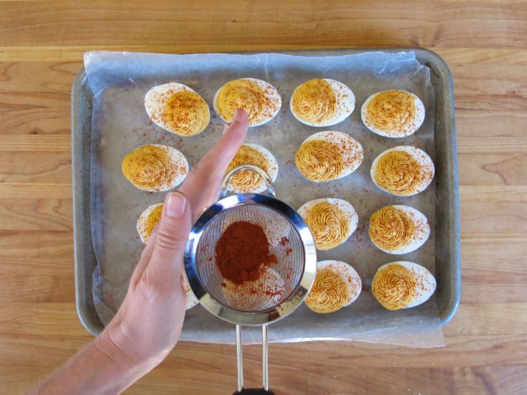 Dusting deviled eggs with paprika.