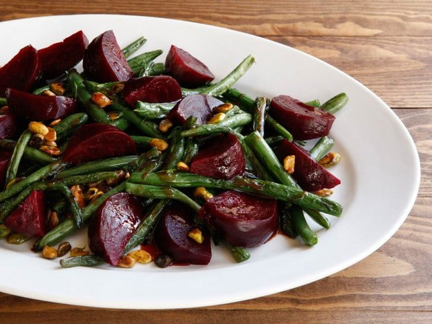 A salad of roasted beets, roasted green beans, and pistachios on a white serving plate atop a wooden table.
