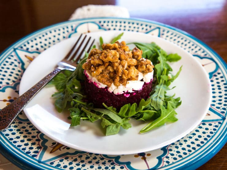 Roasted beet tartare with goat cheese and candied nuts presented on a bed of greens with fork, on a white and decorative Moroccan plate.