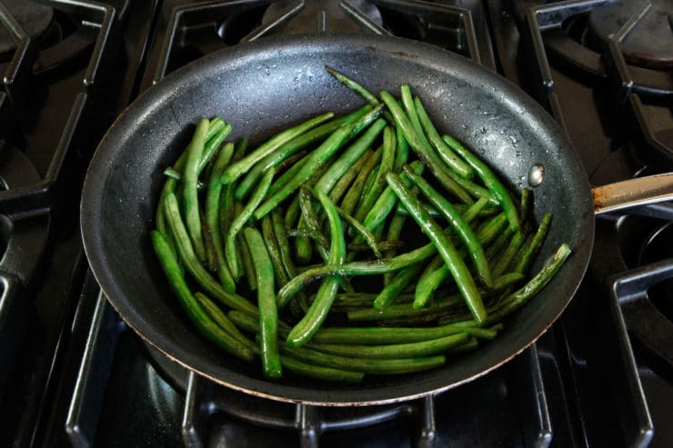 Sauteeing green beans on the stove.