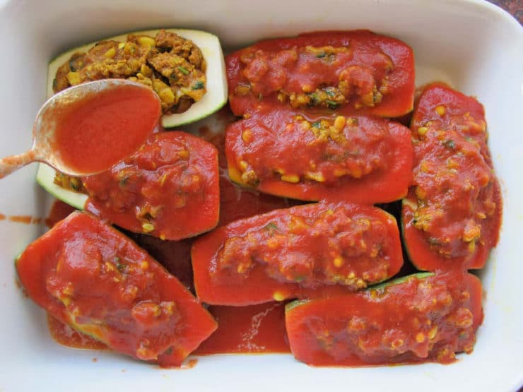 Tomato sauce spooned over stuffed zucchini in a baking dish.