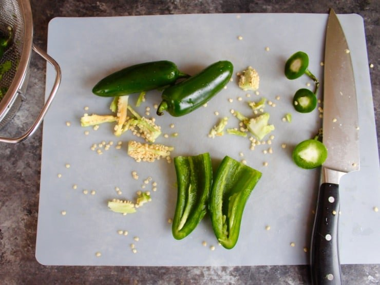 Jalapeno peppers sliced with seeds removed on cutting board on countertop with chef's knife