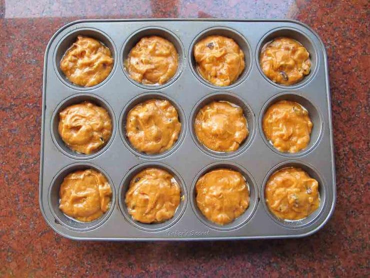 Pumpkin cupcake batter in a cupcake tin.