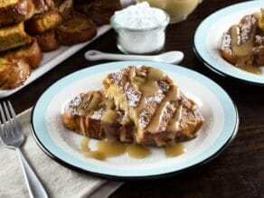 Wider horizontal shot - plate of challah french toast drizzled with Kahlua cream sauce, napkin and platter of french toast in background, powdered sugar with small spoon behind.