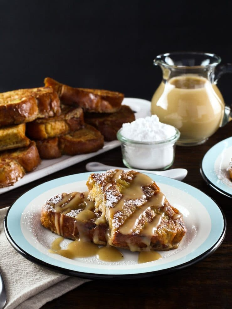 Vertical shot - plate of 2 slices of challah french toast drizzled with Kahlua cream sauce, napkin and platter of french toast in background, powdered sugar with small spoon and carafe of cream sauce behind.