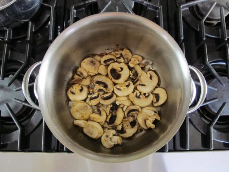 Sliced mushrooms browning in a pot.