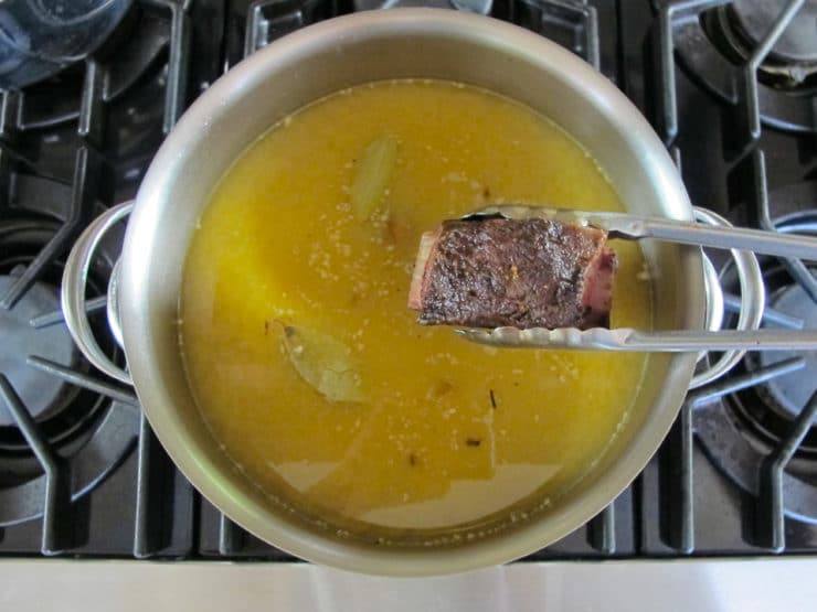 Removing short ribs from pot of soup.