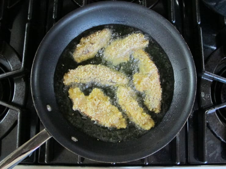Frying portobello slices in a pan.