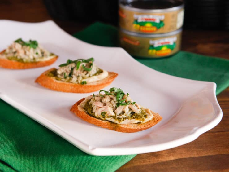 Tuna, Hummus & Pesto Crostini - Crispy Baguette Crostini topped with Genova Tonno Tuna, Hummus and Pesto. Perfect for a light, healthy lunch or snack.