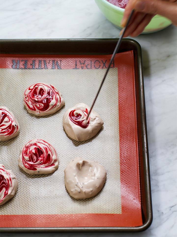 Adding raspberry puree to meringues.