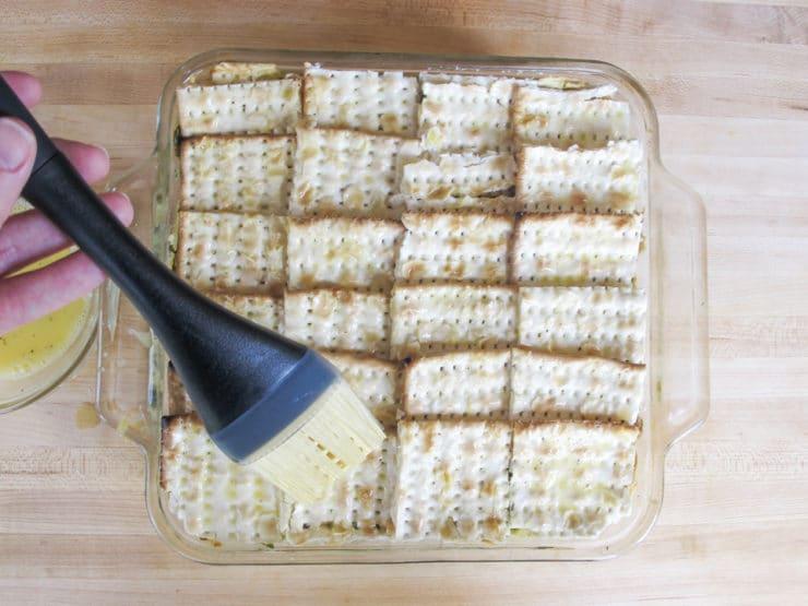 Brushing egg whites over matzo.