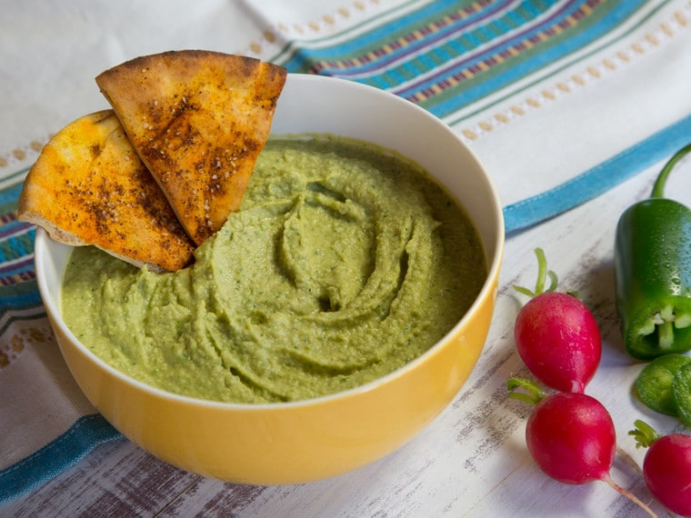 Green jalapeno hummus in a yellow bowl.