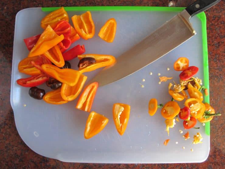 Mini sweet peppers on a cutting board.
