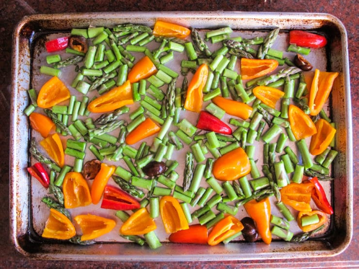 Peppers and asparagus on a baking sheet.
