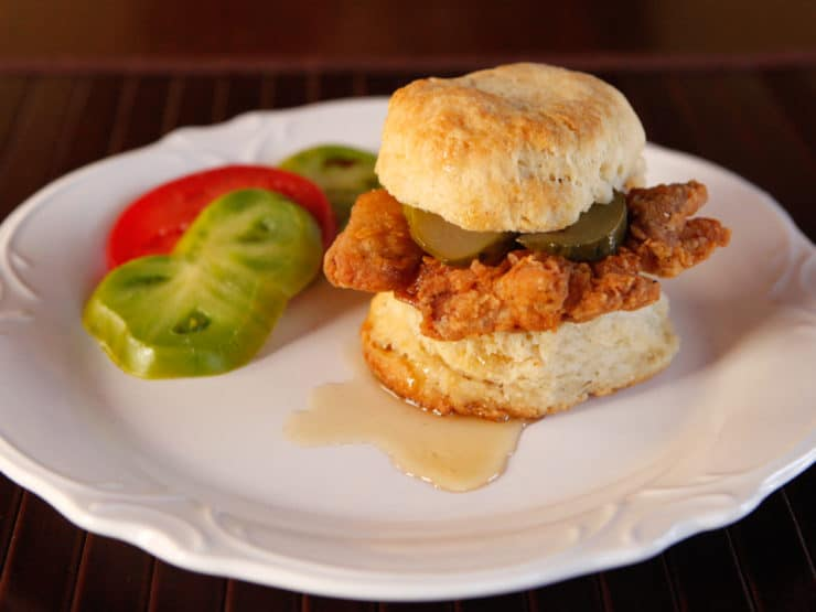 Fried Chicken Sliders Recipe - Crispy, Flavorful Fried Chicken Thighs on Freshly Baked Biscuits with Pickle Slices and a Drizzle of Honey. #southern #comfortfood