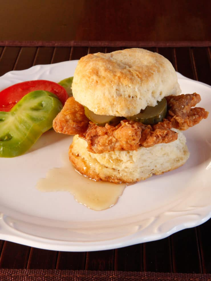 Fried Chicken Sliders - Crispy, flavorful fried chicken thighs on freshly baked biscuits with pickle slices and a drizzle of honey.