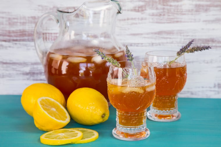 A pitcher of iced tea next to two glasses of iced tea garnished with fresh lavender sprigs.