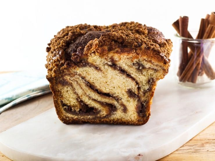Babka loaf sliced, swirly cinnamon filling, on white marble cutting board with glass carafe of cinnamon sticks and cloth napkin in background.