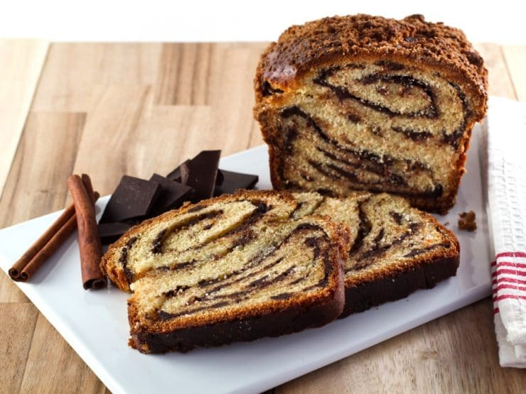Frontal shot of sliced babka with swirling chocolate filling, chocolate chunks and cinnamon sticks, and cloth napkin on white cutting board with wood background.