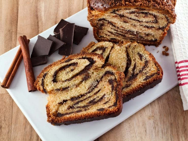 Horizontal shot of sliced babka with swirling chocolate filling, chocolate chunks on white cutting board with wood background.