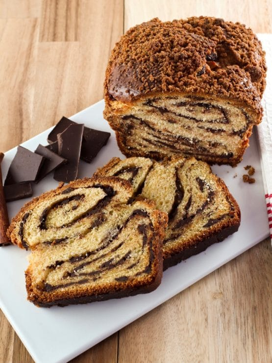Overhead vertical shot of sliced chocolate babka with chocolate chunks on white cutting board with wood background.