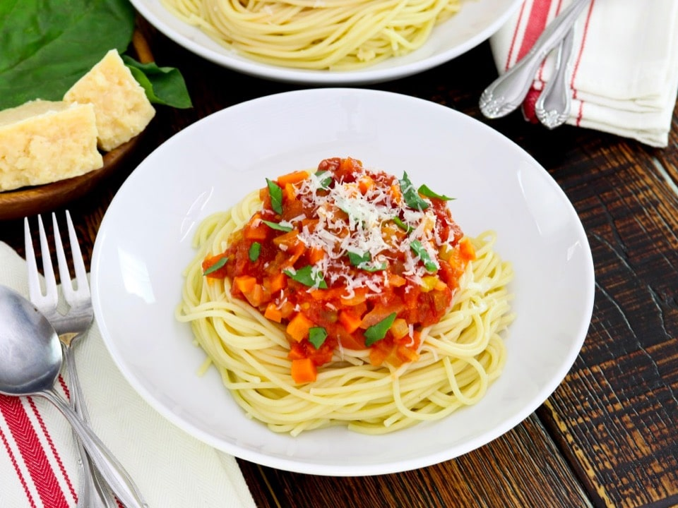 Overhead shot - close up, white plate of spaghetti pasta with cooked pomodoro tomato sauce topped with fresh basil and parmesan, cloth napkin with utensils beside it, another plate of pasta, parmesan block and fresh basil in background.