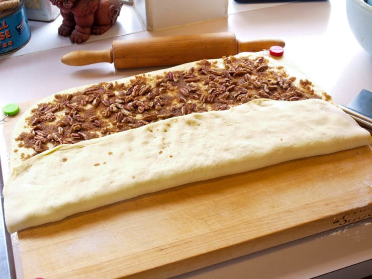 Pecan roll dough with one edge folded.