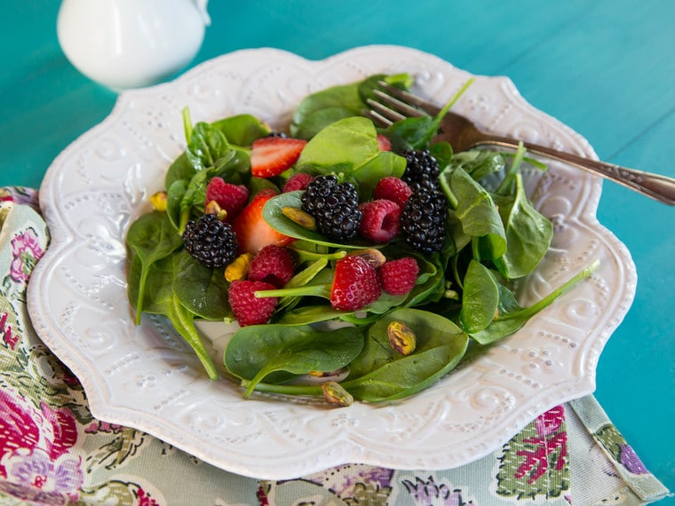 A fresh spinach salad topped with berries on a white plate.