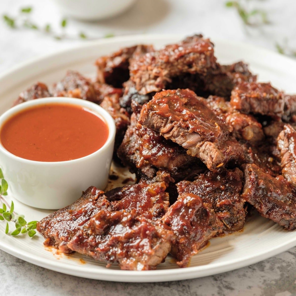 Square Crop- White plate of oven barbecued short ribs with sauce, garnished with fresh thyme, on a marble countertop.