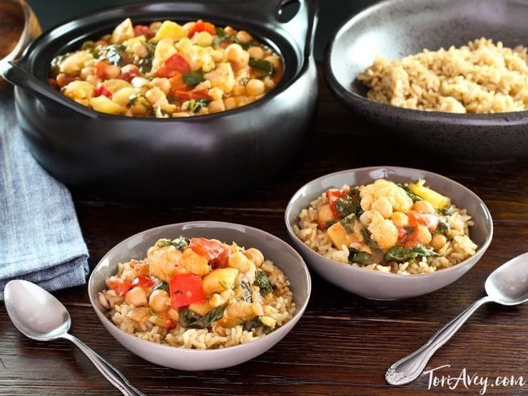 Wide shot of vegan Curried Vegetable Stew, served with brown rice.
