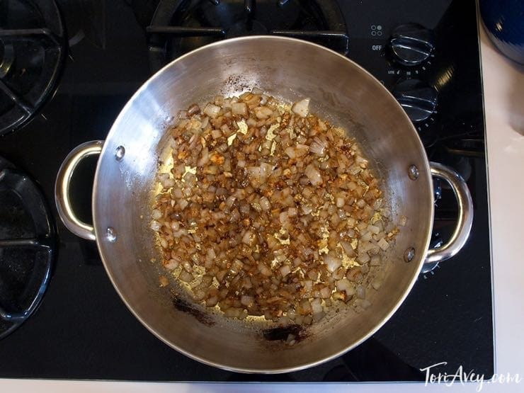 Onions and spices cooking in pot on stovetop, overhead shot.