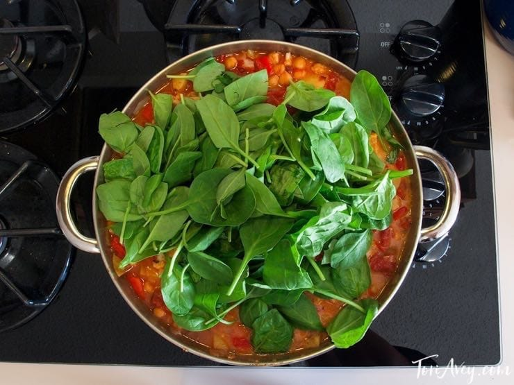 Curried Vegetable Stew cooking in pot on stovetop with fresh greens and coconut milk.