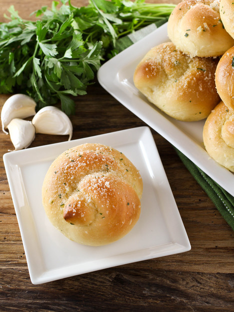 Garlic Knots – Yeast-Risen Rolls with a Buttery, Garlic Herb Topping. Nostalgic, Family-Inspired Recipe from Contributor Kelly Jaggers.