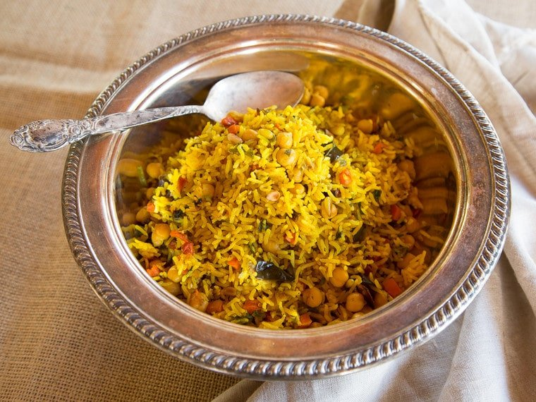 Golden rice mixed with roasted vegetables and chickpeas in a silver serving bowl with a silver serving spoon atop a cream muslin tablecloth.