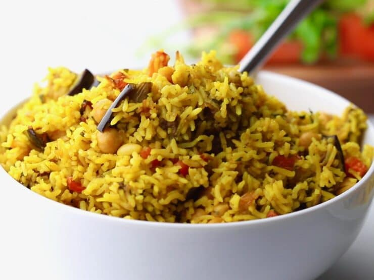 Horizontal close up - spoon digging into fluffy yellow vegetable rice with pieces of eggplant and carrot.