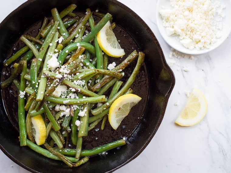 Seared green beans and cotija cheese with lemon wedges in a black cast iron skillet on a white marble background.