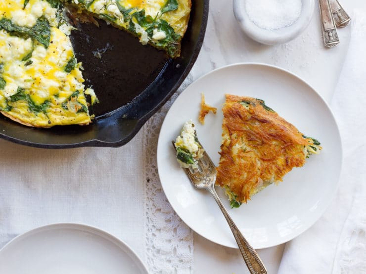 Slice of potato crusted frittata on a white plate next to a whole frittata in a black cast iron pan on a white tablecloth.