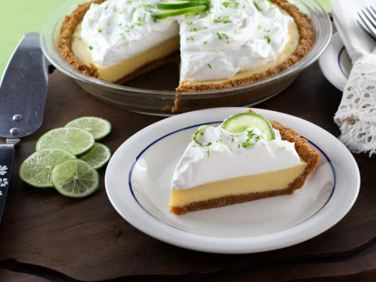 A slice of key lime pie on a white plate.