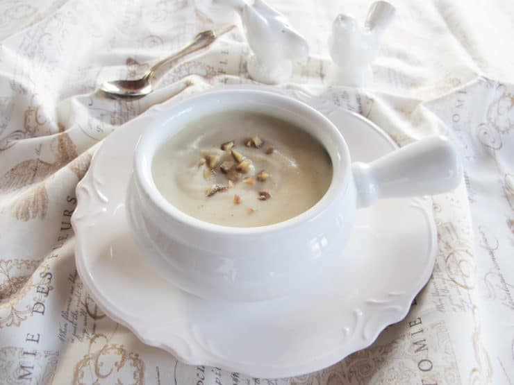 Jerusalem artichoke soup in a white bowl on a small white plate next to a silver spoon on a white cloth background.