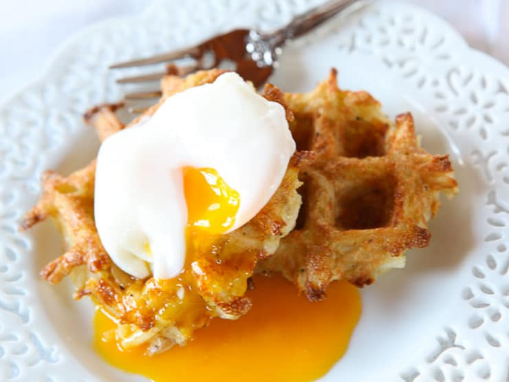 Latke waffle topped with a poached egg on top of a white plate.