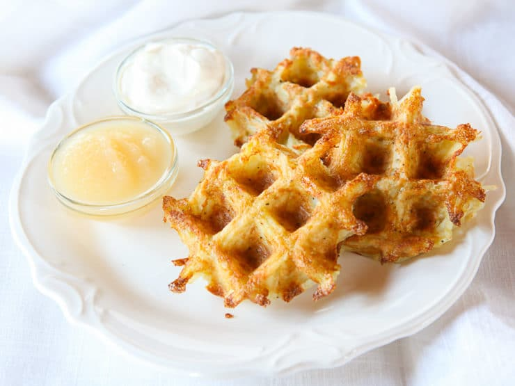 Latke waffles on a white plate with a small dish of sour cream and a small dish of apple sauce on a white cloth background.