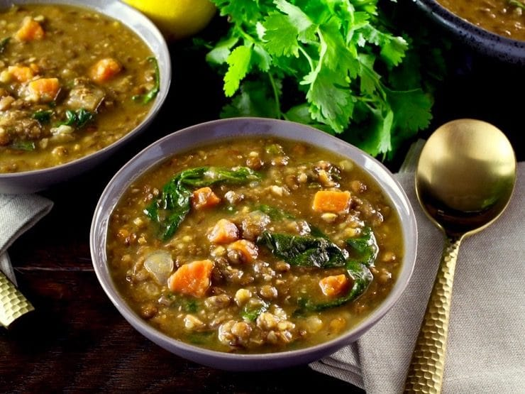Lentil Spinach Soup in a bowl on a wooden table next to a gold spoon sitting on a napkin with fresh parsley in the background.