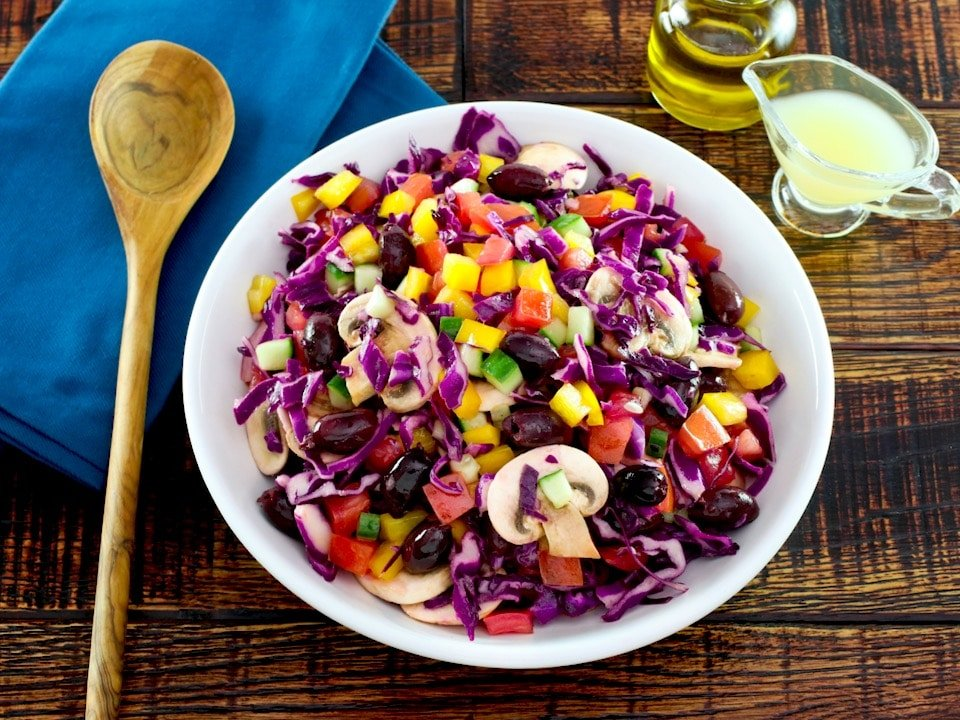 Overhead shot of bowl of colorful rainbow salad with peppers, cucumbers, mushrooms and cabbage in a white bowl with glass dish of lemon juice, carafe of olive oil and blue napkin with wooden spoon in the background.