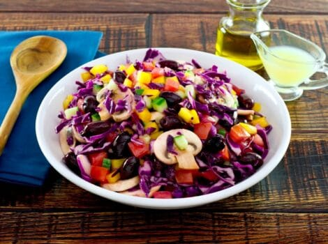 Bowl of colorful rainbow salad with peppers, cucumbers, mushrooms and cabbage in a white bowl with glass dish of lemon juice, carafe of olive oil and blue napkin with wooden spoon in the background.