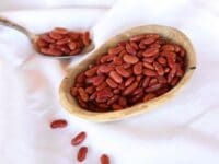 Horizontal shot - Wooden dish of dried Kidney Beans on a white cloth background, spoon of beans in background.