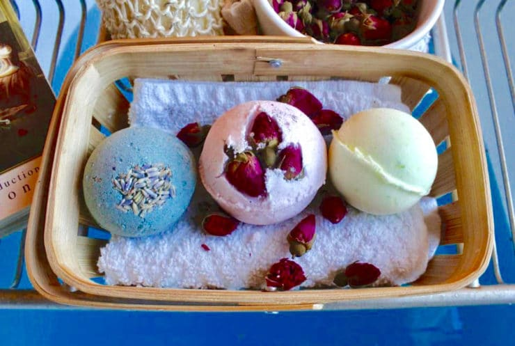 Three botanical bath fizzies resting on towel with flower petals in basket on wire shelf over blue bathwater.